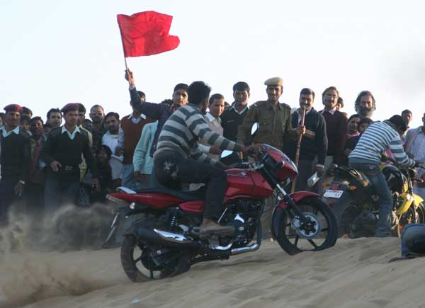 Local Youth enjoying bike race during Camel festival at sand dunes of Ladera village